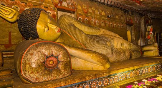 A statue of reclining Buddha in the ancient Buddhist cave temple at Dambulla, Sri Lanka.